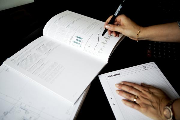 en person läser och antecknar, bara händer synliga